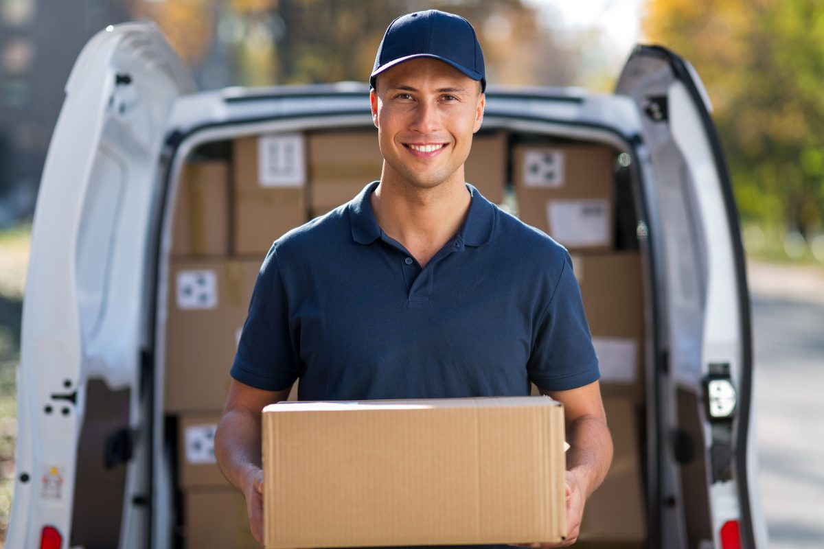 Man with package standing in fron of same day delivery van